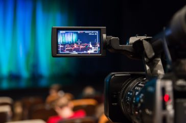 Video camera in the auditorium. Spectators gather in the hall before the performance. LCD display on the camera.